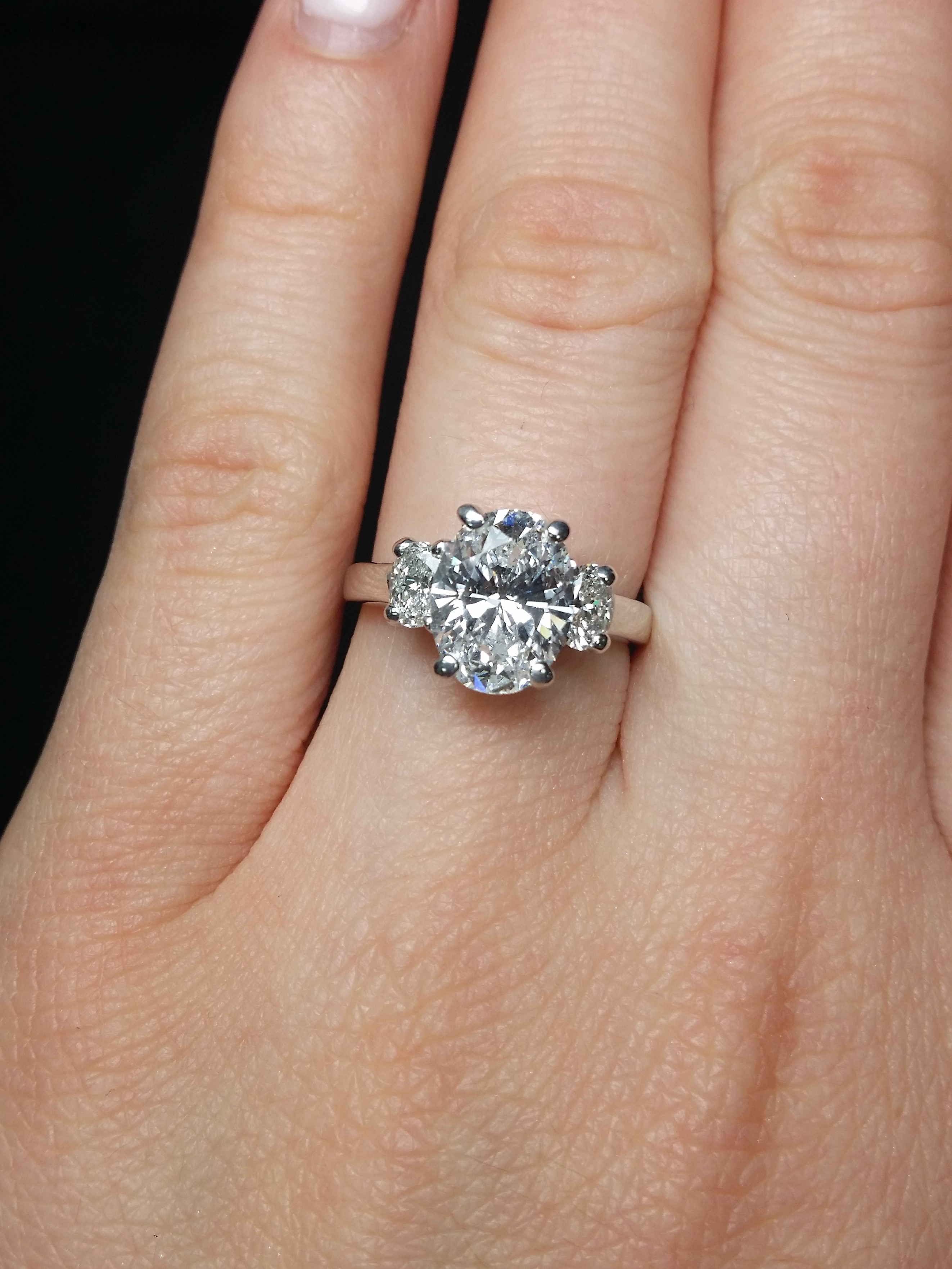 Dream engagement ring with three sparkling oval cut diamonds