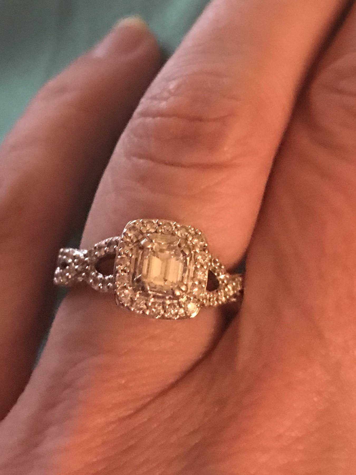 Emerald cut ring surrounded by bezel diamonds with infinity setting